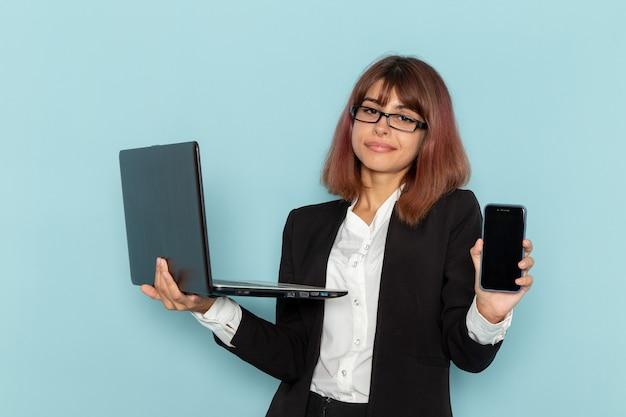 Impiegato di ufficio femminile di vista frontale che tiene smartphone e computer portatile sulla superficie blu