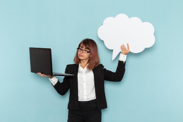Impiegato di ufficio femminile di vista frontale che tiene segno bianco e computer portatile sulla superficie blu-chiaro