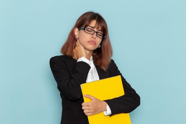 Женский офисный работник, вид спереди, держащий желтый документ и имеющий боль в шее на голубой поверхности