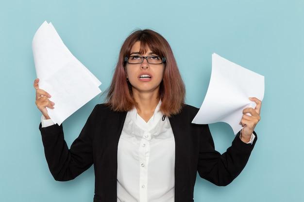 Вид спереди женский офисный работник в строгом костюме, держащий документы на синей поверхности