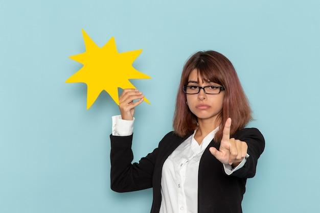 Вид спереди офисный работник женского пола в строгом костюме с желтым знаком на синей поверхности