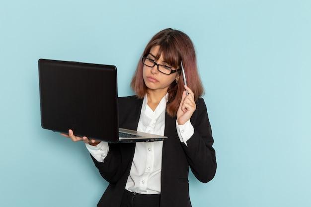 ノートパソコンを使用し、水色の表面で考える厳しいスーツを着た女性サラリーマンの正面図