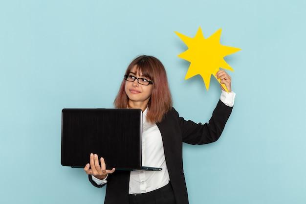밝은 파란색 표면에 노란색 기호를 들고 노트북을 사용하는 엄격한 소송에서 전면보기 여성 회사원