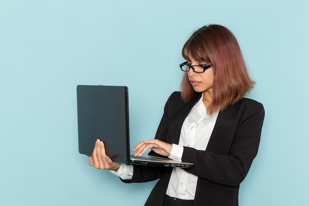 밝은 파란색 표면에 노트북을 사용하는 엄격한 소송에서 전면보기 여성 회사원