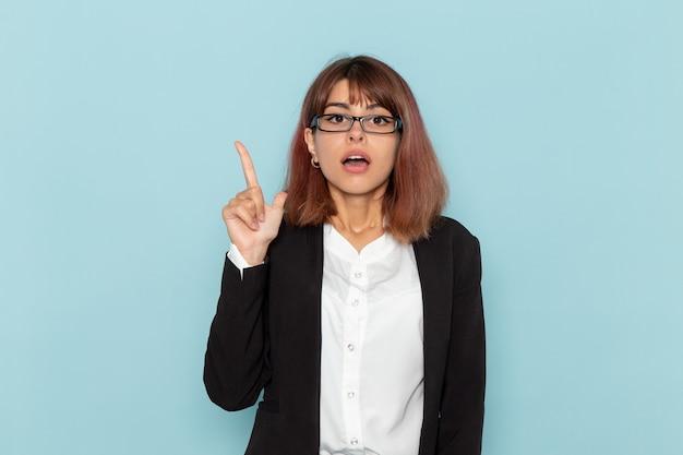 青い表面で指を上げる正面図の女性サラリーマン