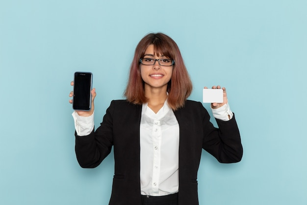 Front view female office worker in strict suit holding card and phone on blue surface