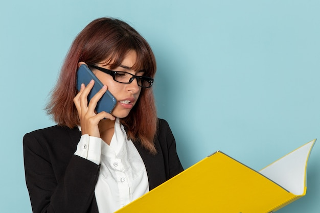 Front view female office worker in strict suit holding documents while talking on the phone on blue desk