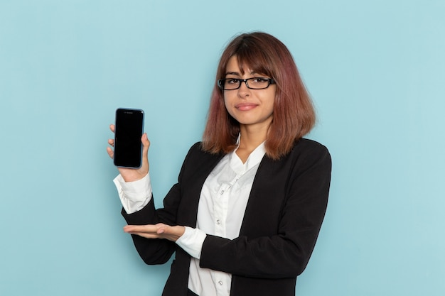 Front view female office worker in strict suit holding her smartphone on blue surface