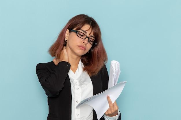Impiegato di ufficio femminile di vista frontale in vestito rigoroso che tiene il lavoro di ufficio sulla superficie blu