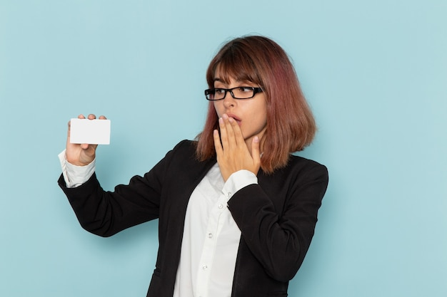 Front view female office worker in strict suit holding white card on blue surface