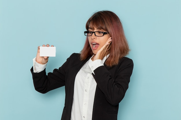Front view female office worker in strict suit holding white card on the blue surface