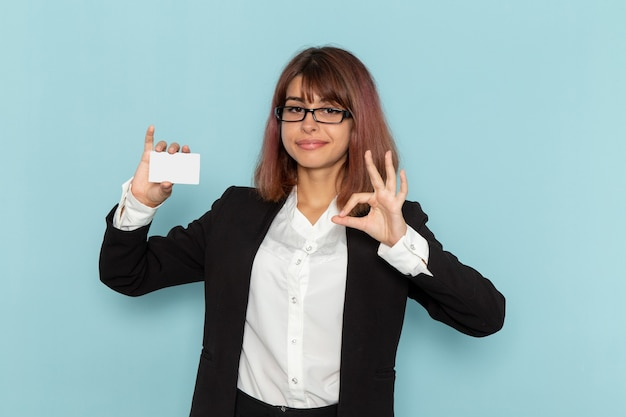 Front view female office worker in strict suit holding white card on light blue surface