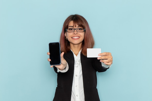 Front view female office worker in strict suit holding white card and phone on blue surface