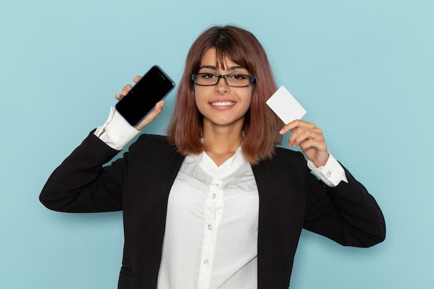 Front view female office worker in strict suit holding white card and phone on light blue surface