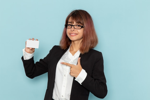 Front view female office worker in strict suit holding white plastic card on blue surface