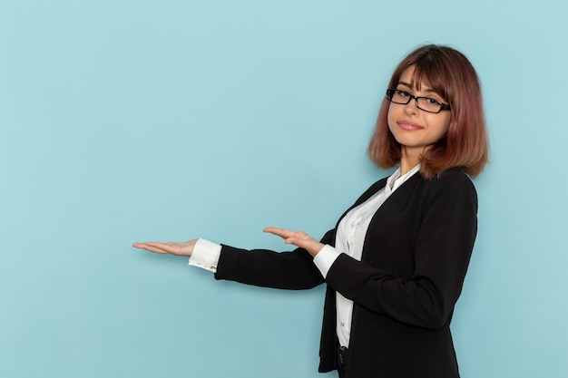 Front view female office worker in strict suit posing on light-blue desk