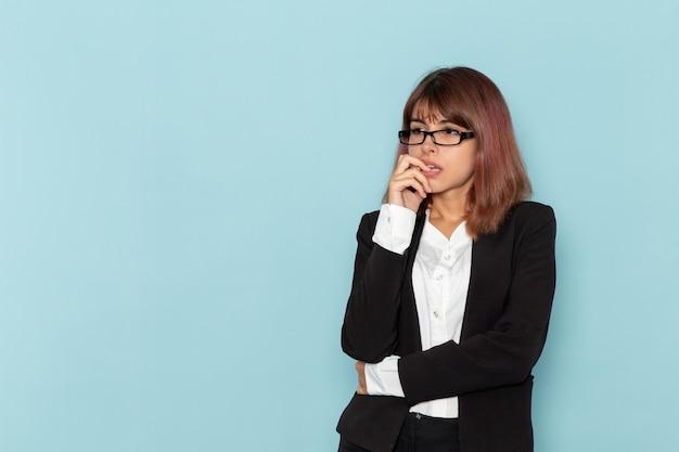 Impiegato di ufficio femminile di vista frontale in vestito rigoroso che posa sulla superficie azzurra