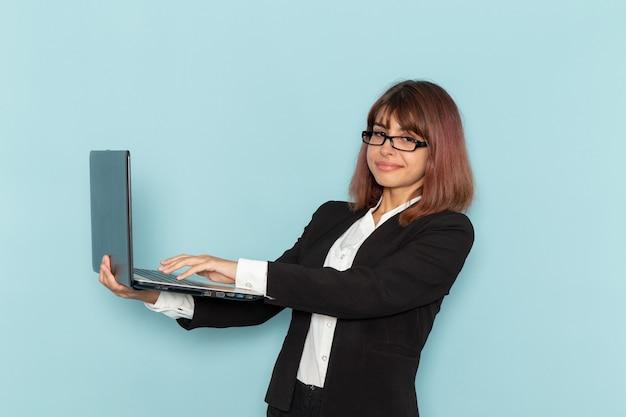 Impiegato di ufficio femminile di vista frontale in vestito rigoroso che sorride e che utilizza computer portatile sulla superficie blu