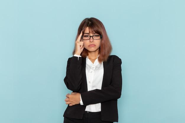 Impiegato di ufficio femminile di vista frontale in vestito rigoroso che pensa stressante sulla superficie blu