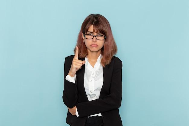 Impiegato di ufficio femminile di vista frontale in vestito rigoroso che minaccia sulla superficie blu