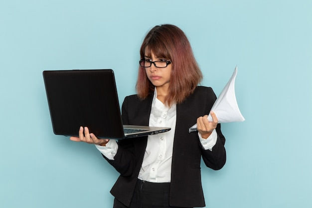 Impiegato di ufficio femminile di vista frontale in vestito rigoroso usando il computer portatile e che tiene i documenti sulla superficie azzurra