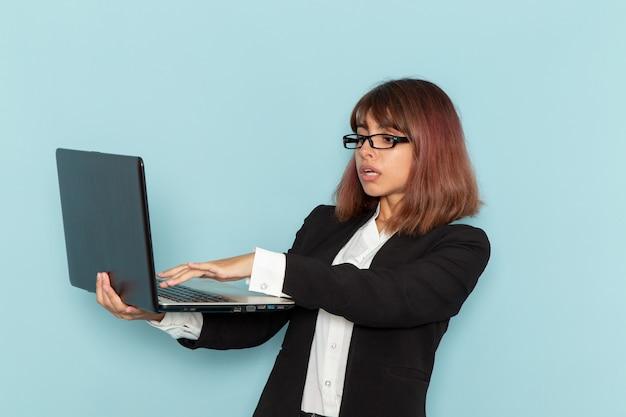 Impiegato di ufficio femminile di vista frontale in vestito rigoroso usando il computer portatile sulla superficie blu-chiaro