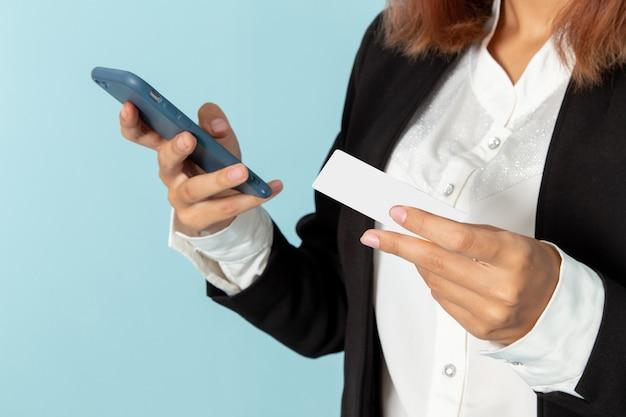 彼女の電話を使用し、青い表面にカードを保持している正面図の女性サラリーマン