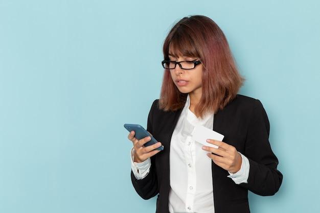 彼女の電話を使用し、水色の表面にカードを保持している正面の女性サラリーマン
