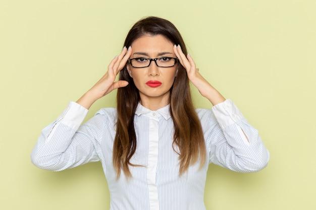 Vista frontale dell'impiegato femminile in camicia bianca e gonna nera che piange e che ha mal di testa sulla parete verde