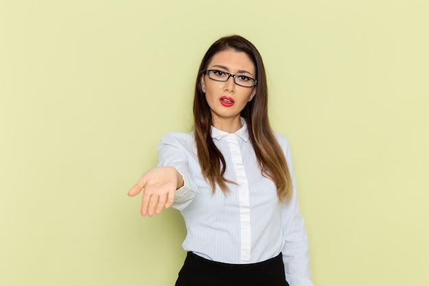 Vista frontale dell'impiegato femminile in camicia bianca e gonna nera sulla parete verde