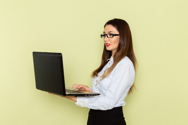 Front view of female office worker in white shirt and black skirt holding laptop on light green wall