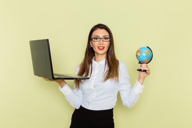 Vista frontale dell'impiegato femminile in camicia bianca e gonna nera che tiene laptop e piccolo globo sulla parete verde chiaro