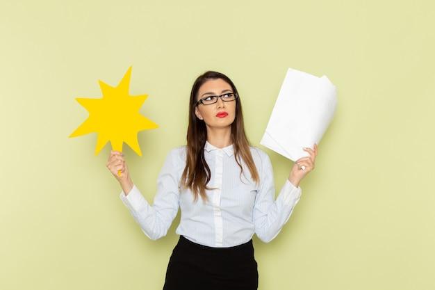 Vista frontale dell'impiegato femminile in camicia bianca e gonna nera che tiene documenti e cartello giallo sulla parete verde