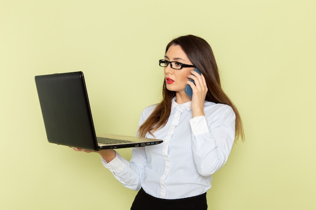 Vista frontale dell'impiegato femminile in camicia bianca e gonna nera che tiene e che utilizza computer portatile sulla donna di lavoro di lavoro di lavoro di affari dell'ufficio della scrivania verde