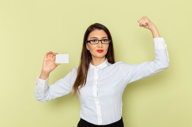 Vista frontale dell'impiegato femminile in camicia bianca e gonna nera che tiene carta bianca e che flette sulla parete verde chiaro