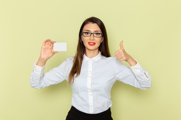 Vista frontale dell'impiegato femminile in camicia bianca e gonna nera che tiene carta di plastica bianca sulla parete verde chiaro