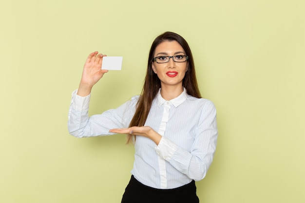 Front view of female office worker in white shirt and black skirt holding white plastic card on light green wall
