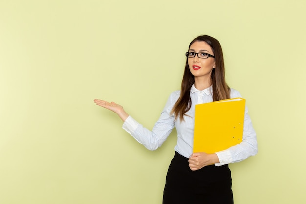 Front view of female office worker in white shirt and black skirt holding yellow file on green wall