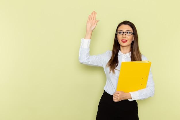 Vista frontale dell'impiegato femminile in camicia bianca e gonna nera che tiene file giallo sulla parete verde chiaro