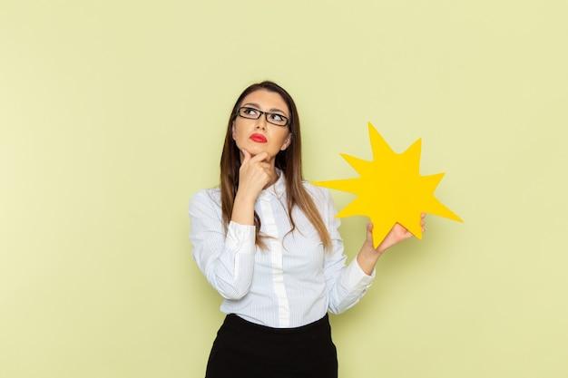 Vista frontale dell'impiegato femminile in camicia bianca e gonna nera che tiene segno giallo e pensa sulla parete verde