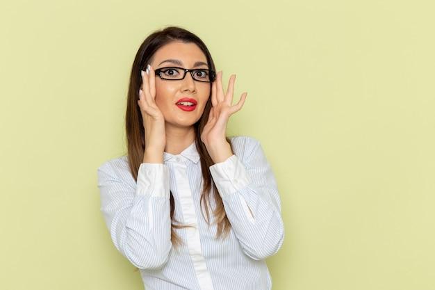 Vista frontale dell'impiegato femminile in camicia bianca e gonna nera sulla parete verde chiaro