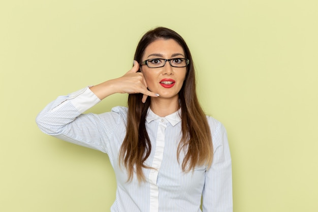 Vista frontale dell'impiegato femminile in camicia bianca e gonna nera in posa sulla parete verde chiaro