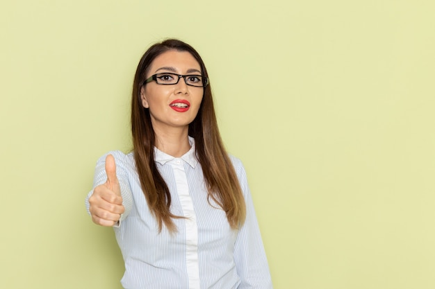 Vista frontale dell'impiegato femminile in camicia bianca e gonna nera in posa e sorridente sulla parete verde