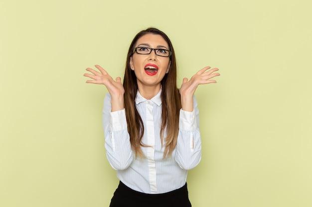 Vista frontale dell'impiegato femminile in camicia bianca e gonna nera che posa con l'espressione felice sulla parete verde