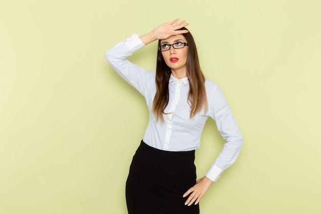 Vista frontale dell'impiegato femminile in camicia bianca e gonna nera in posa con espressione stanca sulla parete verde