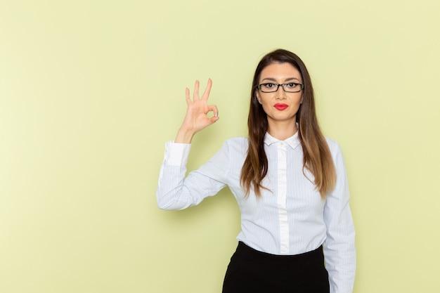 Vista frontale dell'impiegato femminile in camicia bianca e gonna nera che sorride sulla parete verde