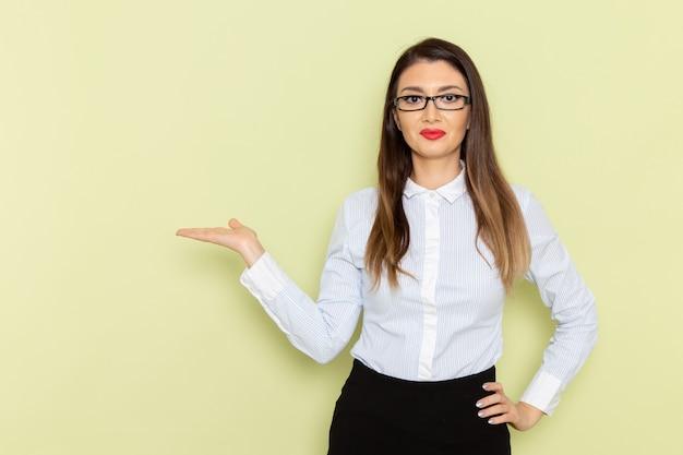 Vista frontale dell'impiegato femminile in camicia bianca e gonna nera che sorride e che posa sulla parete verde