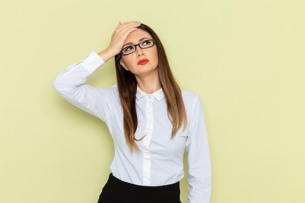 Vista frontale dell'impiegato femminile in camicia bianca e gonna nera ha sottolineato sulla parete verde