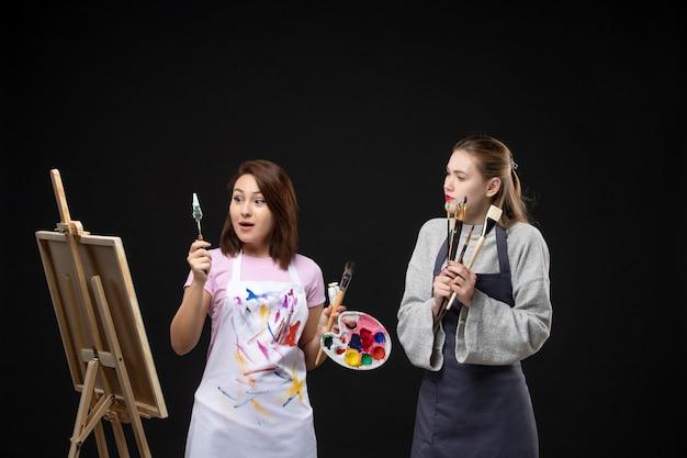 Vista frontale pittrice disegno su cavalletto con altra donna su sfondo nero artista foto colore arte immagine dipinge lavoro disegnare