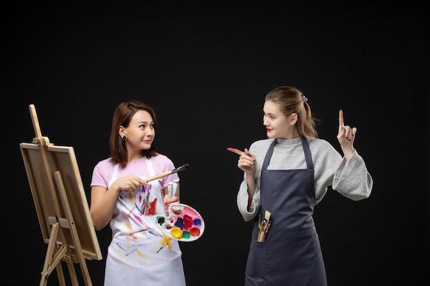 Vista frontale pittrice che disegna su cavalletto con un'altra donna su muro nero foto a colori immagine artistica artista dipingere disegnare